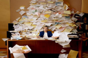 lady at desk with a mess of paper piled behind her